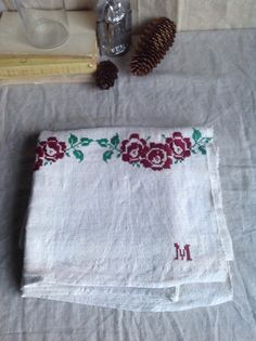 Lovely French linen panel Red Roses & Green Leaves hand embroidery, it also has initial M embroidered on bottom right Hand loomed antique linen fabric made up of two joined panels 132cm x long 99 cm wide (52 x 39) Perfect as a throw, small table cloth or decorative panel Totally rustic   Please note this is a natural fiber and as such there may be some irregularities