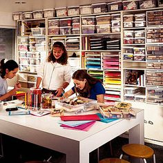 A family of crafters revels in this workshop. They can see what's available to work with at a glance, thanks to a wall of white modular shelving units and many see-through boxes, bins, and letter trays that organize colorful supplies and tools.