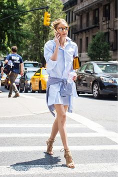 Olivia Palermo belts a blue shirtdress with a blue checked blouse, and finishes the look with mirrored sunglasses and nude Aquazurra sandals