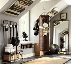 I love the take on this home gym - a neat retro/historic feel! Esp love the hand weights hanging on the wall on the wood! Masculine but still a very awesome looking space.