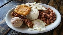 Bandeja paisa, (Paisa refers to a person from the Paisa Region and bandeja is Spanish for platter) with variations known as bandeja de arriero, bandeja montañera, or bandeja antioqueña, is a typical meal popular in Colombian cuisine, especially of the Antioquia department and the Paisa Region, as well as with the Colombian Coffee-Growers Axis, (Caldas Department, Quindío, Risaralda) and part of Valle del Cauca.  The main characteristic of this dish is the generous amount and variety of food…