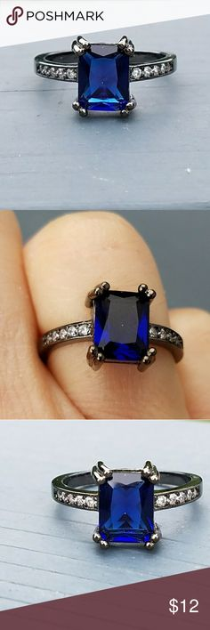 New black gold filled blue cubic zirconia ring This is a new rectangle shaped blue cubic zirconia ring. There are small clear stones on the sides of the ring. The ring is black gold filled metal. Jewelry Rings