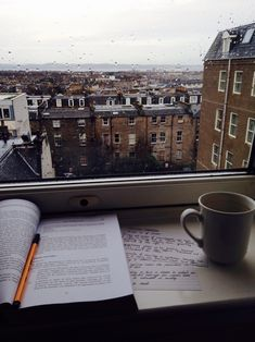 To study on a windowsill with a cup of coffee and this view of a rainy city..