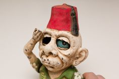 Vintage, cast iron zombie mechanical bank. His name is Alberto, he sports a shriner fez hat and he is quite bizarre in that he puts the coin into his eye socket!