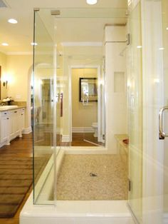 Glass shower doors create a streamlined look for this master bathroom.  Recessed lights reflect off of glass doors and the shower floor is lined with small ceramic tile.  White cabinets contrast nicely with wood floor.