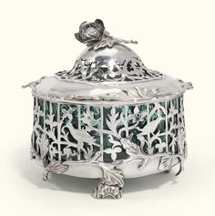 A Dutch silver butter dish, Anthonie van Luttervelt, Utrecht, 1770 circular, the body pierced and chased with birds and flowers, sprig and leaf borders, foliate finial, on three leaf-capped scroll feet, with green glass liner, 1795 Dutch control mark