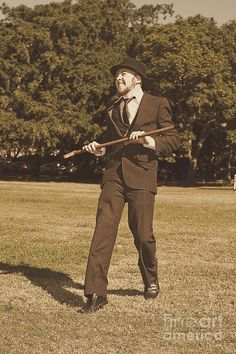 A Man Wearing A Dress Suit And Bowler Hat, Dancing In An Open Field While Carrying A Cane. Sepia Tone For Antique Effect by Ryan Jorgensen