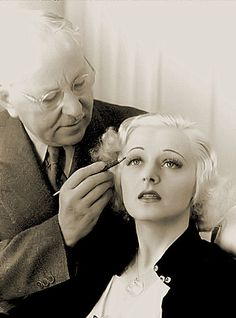 Max Factor applying makeup.  In the early years of the business Factor personally applied his makeup to actors and actresses. He developed a reputation for being able to customize makeup to present actors and actresses in the best possible light on screen. Among his most notable clients were Gloria Swanson, Mary Pickford, Pola Negri, Jean Harlow, Claudette Colbert, Bette Davis, Norma Shearer, Joan Crawford, and Judy Garland.