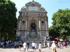 In this photo you can see the Fountaine Saint Michel which is the tallest fountain in Paris showing just how large it is in comparison to the tourists passing by as well as some of the intricate details.  See more Paris Photos at www.eutouring.com/images_fontaine_saint_michel.html
