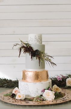 Absolutely breath taking wedding cake with uneven layers, French toile patterned tiers, and a copper metallic foil layer. The asymmetrical floral accent completes the look and adds to the air of untamed romance.