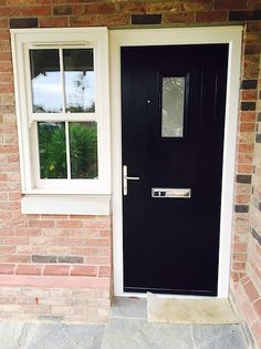 Black Composite Front Door with flanking cream PVC-U sliding sash window  - a…