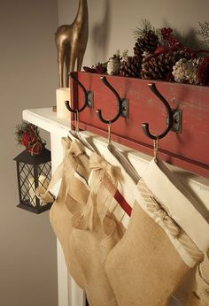add hooks to a wooden box filled with decorations to hang stockings from the mantle