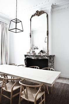 Minimalist dining space with a fireplace, a large vintage mirror and a simple dining room table