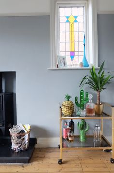 Our retro bar cart in our living room - gold frame with smoked glass shelves. Very similar to a West Elm bar cart but costing £20 from a vintage store! Read on to see how to style your bar cart / cocktail trolley.