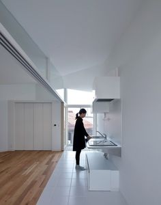 A partition separates a kitchen and dining area with full-height glazed doors at either end from the main living and sleeping zone