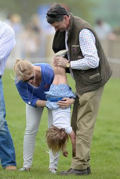 What fun: Squealing with delight, Mia is upended by Tim Laurence and her aunty Autumn Phillips