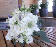 A beautiful white bridal bouquet with purple wildflower accents designed by Eastern Floral for a wedding at The Goei Center.