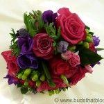 A vibrant bridal bouquet of purple anemone, purple power roses, purple lissianthus & green hypericum