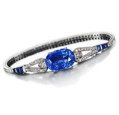 An art deco sapphire and diamond bracelet, Cartier, French, circa 1925  centering a cushion-cut sapphire, joining a slender looped line of old European and single-cut diamonds, accentuated by calibré-cut sapphires; signed Cartier Paris London New York, no. 4262, with French assay mark and maker's mark for Renault, within original fitted box; sapphire weighing approximately: 17.20 carats; estimated total diamond weight: 2.60 carats; mounted in platinum
