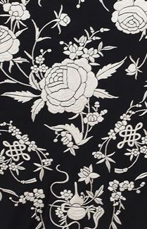 Hand-embroidered Chinese shawl, c. 1920s. Made from black silk crepe with ivory padded satin stitch embroidery, the superbly designed shawl features a graphic floral design whose compelling verisimilitude nature herself would envy. Around each plump rose trail the delicate and caressing tendrils whose subtle sinuosities intimate an enigmatic and pleasing truth that we sense but cannot understand.