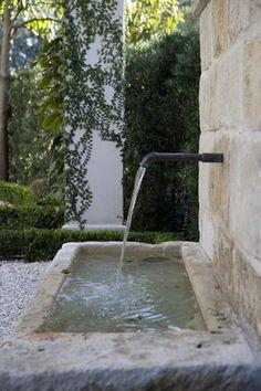 Simple stone trough fountain w/ antique spout.