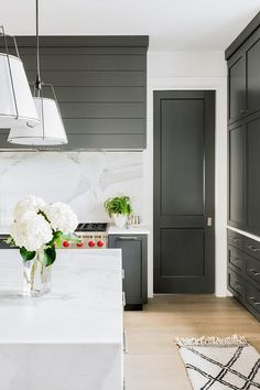 Modern kitchen designed with a black shiplap range hood over black cabinetry finished with brass pulls.