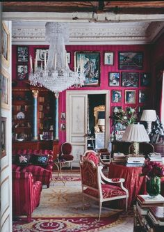 Pink decor with beautiful chandelier and an art gallery wall. Very colorful and eclectic.