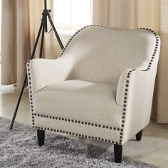 Enjoy the simple pleasure of a piping hot cup of tea in your new favorite chair. This accent chair features a soft, neutral beige linen with a subtle curved back and scroll arms, making it a perfect addition to any room.