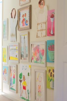 gallery wall of kid art going up the back stairs