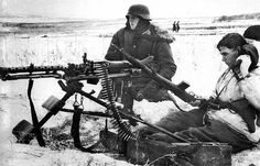 German soldiers, armed with an MG-34 machine gun, in firing position. The soldier on the right is holding a captured Soviet SVT-40 rifle. - The Eastern Front, 1943-1944.