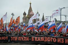 Russia's opposition supporters carry a banner reading These bullets in each of us during a...