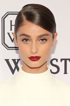 """Who: Taylor Hill What: Evening Glamour How-To: Makeup artist Hung Vanngo and hairstylist Seiji Yamada turned the new model into a """"modern-day Audrey Hepburn"""" for the amfAR gala, giving her a sleek deep part, full brows and patent-red lips.  Editor's Pick: Hourglass Opaque Rouge Liquid Lipstick in Icon, $28, sephora.com.   - HarpersBAZAAR.com"""