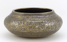 Bowl early 14th century    Brass, inlaid with silver, gold and a black organic material H: 7.2 W: 16.6 D: 16.6 cm Iran