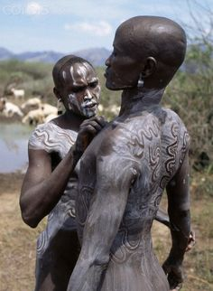 Africa | Mursi men smear their bodies with a mixture of local chalk and water and then draw designs with their fingertips to enhance their physical appearances. Ethiopia. | © Nigel Pavitt