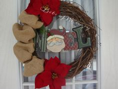 Celebrate a country Christmas with this charming grapevine wreath with accents of burlap, poinsettias and a cute wooden Santa Noel.    All