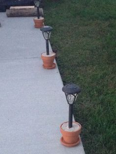 Problem: Solar lights staked in yard are difficult to mow weed eat around. Solution: Terra cotta flower pots a bag of quick-krete. Mix concrete according to the package directions. Scoop into flower pot immediately put light into the center (remove the Pathway Lighting, Outdoor Lighting, Landscape Lighting, Backyard Lighting, Outside Lighting Ideas, Lights For Backyard, Garden Lighting Ideas, Solar Pathway Lights, Backyard Projects