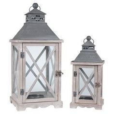 "Two whitewashed candle lanterns with x-shaped window latticing.    Product: Small and large lanternConstruction Material: Wood, glass, and metalColor: Gray and whitewashDimensions: 24"" H x 10"" W x 10"" D (large)"