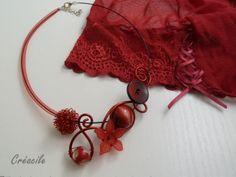 Collier en fil aluminium rouge avec différentes perles et boutons ainsi qu'une fleur assortie et un côté en résille rouge.  Le rouge est une couleur que je trouve définitivement glamour et féminine. J'aime aussi travailler ce côté asymétrique pour donner une touche moins conventionnelle et plus moderne à mes créations. Ici, l'asymétrie se dévoile avec la résille rouge qui ajoute de la sensualité au tour de cou. Les courbes de l'aluminium apportent quant à elle de la volupté au collier.