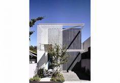 I progettisti hanno optato per un semplice linguaggio architettonico, accostando muratura, legno e pietra per Fairbairn House, a Melbourne. Una parete a sbalzo in mattoni forati anticipa e protegge l'ingresso di casa