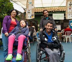 Foto de duas crianças com deficiência em cadeiras de rodas e duas cuidadoras sorrindo