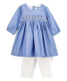 Snug smocking gives oodles of charm to this comfy cotton dress. Coordinating leggings complete the look with sweet style.
