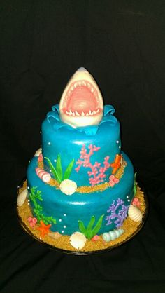 Under the sea shark cake. The top is made of Rice Krispies. Smooth rice crispies into pointed cylinder  shape, then cut into it 3/4 of the way down. Shape rice crispies into the shape of a shark mouth and open the crease  as you go. Cover the whole thing in marshmallow fondant and smooth out any bumps