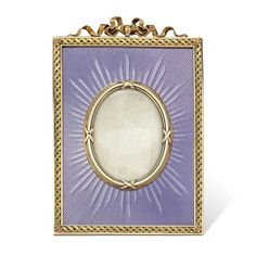 An important Faberge gold and enamel frame, the frame comprising an oval glass photograph pane with yellow gold surround, within a rectangular frame exquisitely laid with a fine lilac enamel with engine-turned background, all to an ornate yellow gold border with ribbon bow surmount, gross weight grams, signed Faberge, circa 1900