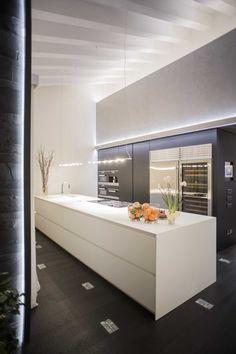 Nella cucina di questa esclusiva abitazione privata esclusiva in stile moderno, l'illuminazione indiretta a LED esalta la presenza delle travi come punto di interesse dell'ambiente.