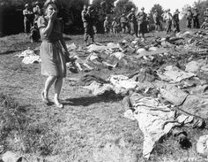 A German girl is overcome as she walks past the exhumed bodies of some of the 800 slave workers murdered by SS guards at Namering, Germany, and laid here so that townspeople could view the work of their Nazi leaders. May 17, 1945.