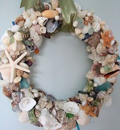 seashell wreath... wreath wrapped in grossgrain ribbon, then the front is covered in shells and decorated with starfish and pearls. very cute!