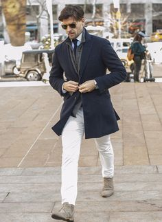 Trim navy topcoat, insulating vest under a grey blazer, and neutral suede chukka boots. Gentleman Mode, Gentleman Style, Modern Gentleman, White Jeans Winter, Winter White, Mens Style Guide, Men Style Tips, How To Wear White Jeans, Only Blazer