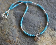 This Tam Davis turquoise beaded necklace has an eye-catching style and easy-to-wear allure. Round beads of sleeping beauty turquoise are covered in a surface of light reflecting facets and are arranged between tiny Hill Tribe silver beads. In the center, a simple silver plated initial