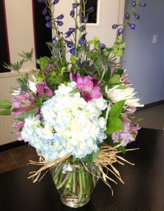Shades of summer abound in this lovely arrangement of hydrangea, delphinium, thistle and alstroemeria decked out in cool shades of blue and lavender.