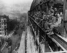 Construction workers on lunch break on the edges of the building they're working on, London 1929